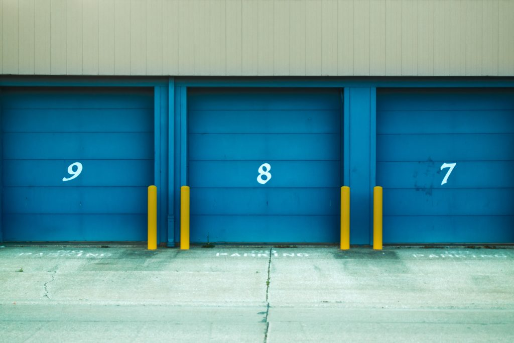numbers on garage doors with yellow bollards showing 11:11